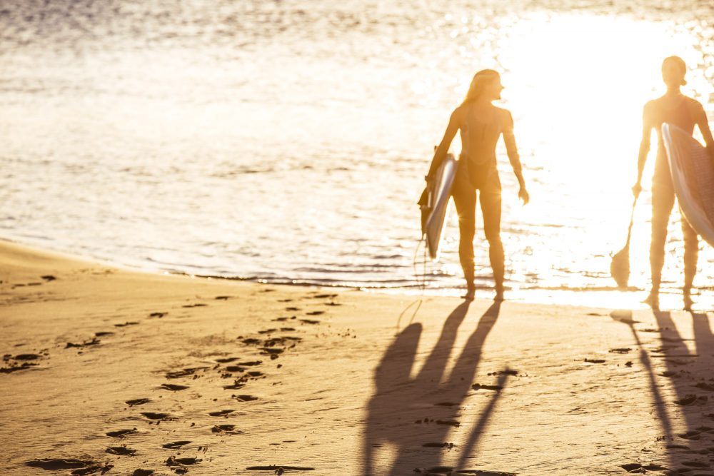 girls-standing-on-beach-with-paddleboards-at-currumbin-creek
