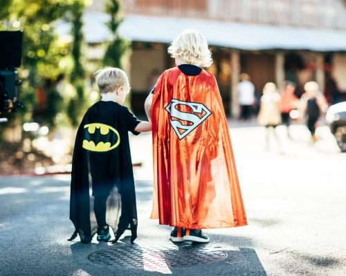 two-boys-holding-hands-wearing-superman-capes-at-movie-world